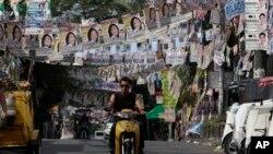 Seorang warga Filipina mengendarai motornya melewati poster-poster kampanye yang menghias jalanan menjelang Pemilu Sela di wilayah suburban kota Quezon, sebelah utara Manila, Filipina (12/5).