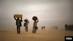 Trabajadores cargan sus pocas pertenencias y huyen caminando de Libia hacia la frontera con Túnez mientras continúan los combates.