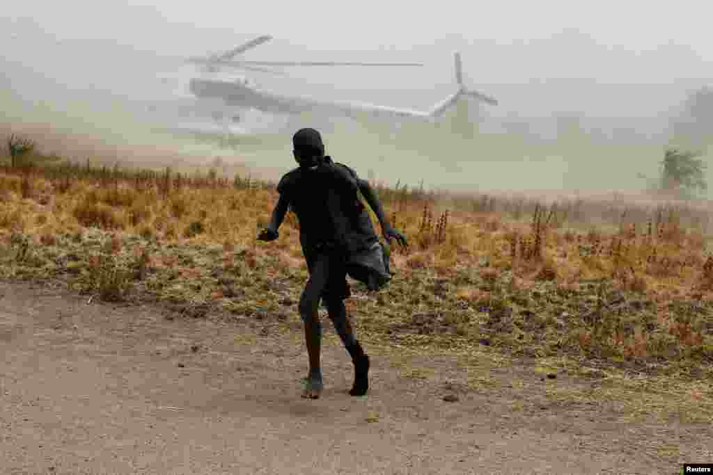 A boy moves away as a United Nations World Food Programme (WFP) helicopter lands in Rubkuai village, Unity State, northern South Sudan.