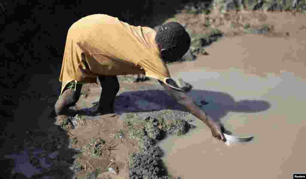 ایک سوڈانی لڑکی ایک کیچڑ کے تالاب سے پانی برتن میں بھر رہی ہے