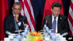 U.S. President Barack Obama, left, and Chinese President Xi Jinping look down during their meeting held on the sidelines of the COP21, United Nations Climate Change Conference, in Le Bourget, outside Paris, on Monday, Nov. 30, 2015. (AP Photo)