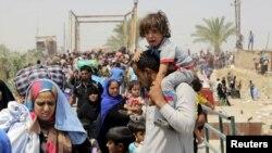 一名逃离拉马迪战火的逊尼派男子携儿带女逃到巴格达郊外(2015年5月24日)