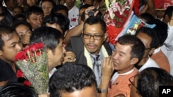 A leader in the Burmese democratic movement, Moe Thee Zun, center, is surrounded by greeting supporters upon his arrival at Yangon International Airport in Rangoon, Burma, September 1, 2012.