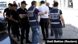 Police officers frisk an employee of the Koza Ipek Group during a raid at the company's office in Ankara, Turkey, September 1, 2015. Turkish police raided the offices of the conglomerate with close links to U.S.-based Muslim cleric Fethullah Gulen, an all