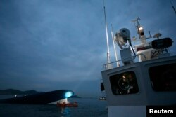 Tàu thuyền quân sự, thương mại và máy bay trực thăng bay vòng mũi tàu, phần duy nhất còn thấy được trên mặt nước.