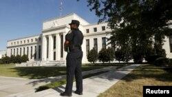 Seorang polisi untuk Federal Reserve berjaga-jaga di depan markas besar bank sentral Amerika ini, di Washington (16/9).