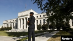 A Federal Reserve police officer keeps watch while posted outside the Federal Reserve headquarters in Washington, Sept. 16, 2015.