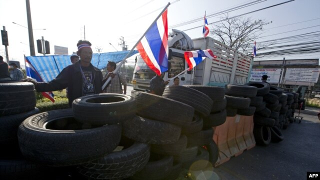 Anti-government protesters wave national flags as they block intersection during rally in Bangkok, Jan. 13, 2014.