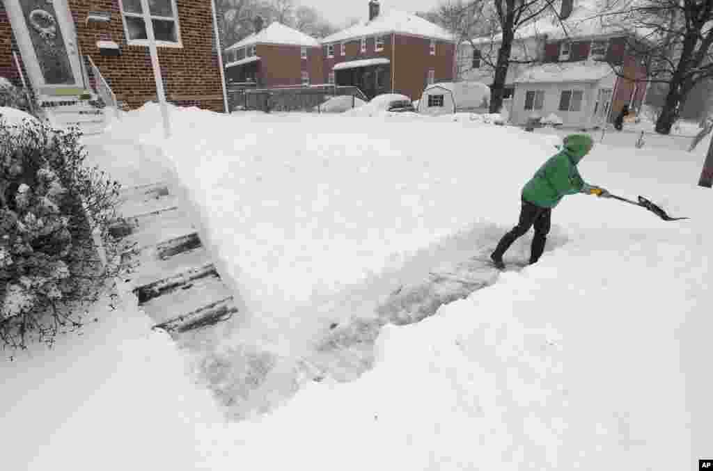 Mae Richardson shovels snow outside her home in Parkville, Md., Saturday, Jan. 23, 2016. (AP Photo/Steve Ruark)