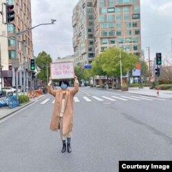 """被指""""造谣""""的武汉医生李文亮殉职后,中国民间主张落实宪法保障公民权利的呼声高涨,有人公开上街举牌要求言论自由。(网络图片)"""