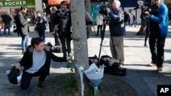 Građani polažu cveće na Šanzelizeu u Parizu, gde je ubijen jedan policajac a dvojica ranjena