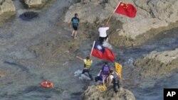 15일 일본 명 센카쿠, 중국 명 댜오위다오에 상륙해 중국기와 대만기를 꽂은 홍콩 시위대.