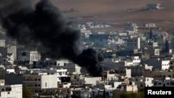 Asap hitam nampak membumbung di atas kota Kobani, terlihat dari wilayah selatan kota Suruc, propinsi Sanliurfa, di perbatasan Turki-Suriah (15/10).