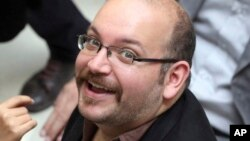 FILE - Jason Rezaian, an Iranian-American correspondent for the Washington Post, smiles as he attends a presidential campaign of President Hassan Rouhani in Tehran, April 11, 2013.
