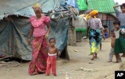 ພາບຈາກວີດີໂອ, 18 ມີນາ18, 2017, Rosmaida Bibi, ທີ 2 ຈາກຊ້າຍ, ຜູ້ຊຶ່ງໄດ້ຮັບຜົນກະທົບ ຈາກການຂາດທາດອາຫານ ດ້ວຍການຊ່ອຍເຫຼືອ ຈາກແມ່ຂອງລາວ Hamida Begum ໃນສູນອົບພະຍົບ Dar Paing, ພາກເໜືອຂອງ Sittwe, ລັດ Rakhinee, ມຽນມາ.