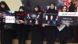 Lebanese women whose relatives were killed at the Iranian embassy attack in Beirut last November hold placards show portraits of their victims, Beirut, Jan. 3, 2014.