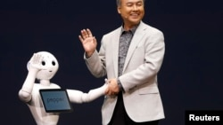 SoftBank Corp. Chief Executive Masayoshi Son (R) waves with the company's human-like robots named 'pepper' during a news conference in Urayasu, east of Tokyo June 5, 2014.
