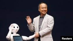 CEO SoftBank Corp. Masayoshi Son (R) dengan robot bernama Pepper produksi perusahaannya dalam konferensi pers di Urayasu, timur Tokyo.