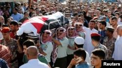 6月2日,约旦士兵和亲属在约旦首都安曼附近为在约叙边界哨所袭击事件中丧生的军人举行追悼会。图为这名军人的战友和家属抬着他的遗体。