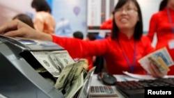 Một nhân viên Ngân hàng Vietinbank đếm tiền USD tại một quầy trao đổi ngoại tệ ở Hà Nội. Bộ Tài chính Mỹ và NHNN Việt Nam vừa đạt được một thoả thuận để giải quyết quan ngại của Hoa Kỳ về hành vi tiền tệ của Việt Nam.