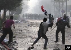 Manifestants attaquant la police à coups de pierres et de bombes incendiaires, près de la Place Tahrir (16 déc. 2011)