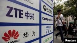 一名中國男子從武漢街頭有著華為和中興標誌的廣告牌前走過。(資料照片)