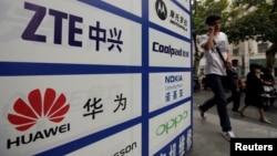 一名中国男子从武汉街头有着华为和中兴标徽的广告牌前走过。(资料照片)
