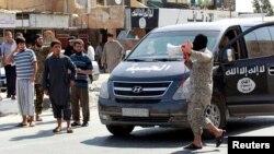 Seorang militan Negara Islam (ISIS) menggunakan pengeras suara untuk mengumumkan pada warga kota Raqqa mengenai pengambilalihan kota Tabqa yang lokasinya dekat (24/9).