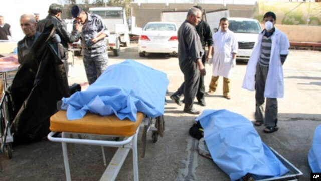 Bodies of bomb attack victims are seen outside a hospital in Tikrit, some 150 km (95 miles) north of Baghdad, 18 Jan 2011