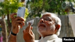 """FILE - Hindu nationalist Narendra Modi, the prime ministerial candidate for India's main opposition Bharatiya Janata Party (BJP), takes a """"selfie"""" with a mobile phone after casting his vote at a polling station during the seventh phase of India's general"""