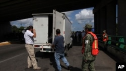 Para petugas imigrasi memeriksa bagian belakang truk kargo untuk mencari migran ilegal di pos perbatasan di Tapachula, Chiapas, Meksiko, 7 Juni 2019. (Foto: AP)