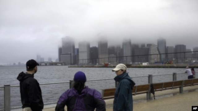 Three local residents stand at  the East River in the Brooklyn borough of New York City after hurricane Irene, downgraded in the city to a tropical storm, passed through, August 28, 2011