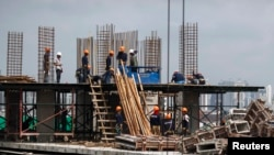 FILE - Construction laborers work at a building site in Bangkok, June 18, 2014.