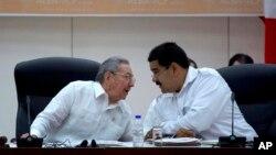 El presidente de Cuba, Raúl Castro, conversa con el mandatario venezolano Nicolás Maduro durante la cumbre del ALBA sobre ébola en La Habana.