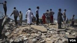 Para pejabat Libya menunjukkan bekas sebuah klinik yang hancur di kota Zlitan, sebelah timur Tripoli, Senin (25/7).