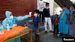 Zdravstveni radnici mere temperaturu dečaku u Indiji, 29.maj 2020. ( Foto: Rojters/Francis Mascarenhas)