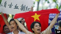 A protester holds a red T-shirt with a yellow star, representing Vietnam's national flag, while chanting anti-China slogans with other demonstrators during a rally against China's claims in the oil-rich South China Sea, in Hanoi, Vietnam, July 2011. (file