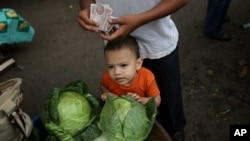 A man, accompanied by a boy, counts bills at the San Isidro market in Tegucigalpa. (file)