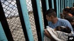 Pripadnik karavana migranata iz Centralne Amerike, držeći dete, gleda kroz pograničnu ogradu prema grupi ljudi koji su se okupili na američkoj strani, dok stoji na plaži gde se pogranična žica završava u okeanu, u Tihuani, Meksiko, 29. aprila 2018.