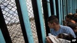 Grupa ljudi kod zida podignutog kod Tijuane na meksičko-američkoj granici
