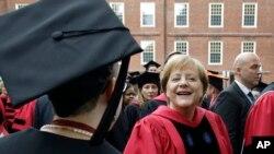 Kanselir Jerman, Angela Merkel, menyambut mahasiswa Harvard yang tengah diwisuda saat ia berjalan dalam prosesi lewat Harvard Yard d awal acara wisuda, 30 Mei 2019, di Cambridge, Mass. (foto: AP Photo/Steven Senne)