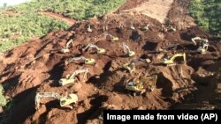 FILE - Excavators search for bodies in Hpakant, Kachin State, Myanmar, Nov. 24, 2015.