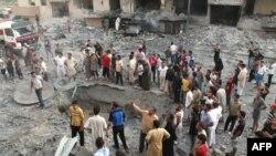 Cư dân tụ tập xung quanh một hố bom tại hiện trường một vụ nổ ở thành phố phía bắc Raqqa, ngày 7/8/2013.
