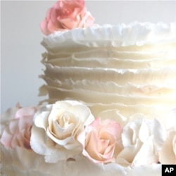 Maggie Austin innovated the frills, or ruffles, technique. The frills are created using paper-thin layers of fondant, which is a sugar paste, and are individually applied to the cake.