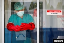Seorang tenaga kesehatan berdiri di dalam bilik usap saat dia bersiap untuk mengumpulkan sampel usap untuk deteksi COVID-19, saat pandemi terus berlanjut di Jakarta, 24 November 2020.