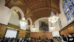 The delegations of Costa Rica, foreground left, Nicaragua, center right, and judges take their seats at the International Court of Justice in The Hague, Netherlands, 11 Jan 2011