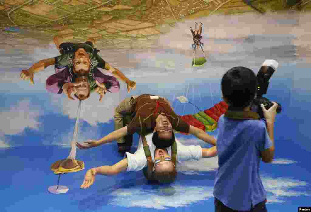 Seorang pengunjung di Taman Hiburan Sentosa di Singapura berpose di sebuah lukisan 3-Dimensi di sebuah museum 'Tipuan Mata'.