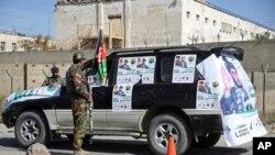 Polícia afegã junto a uma viatura com propaganda eleitoral
