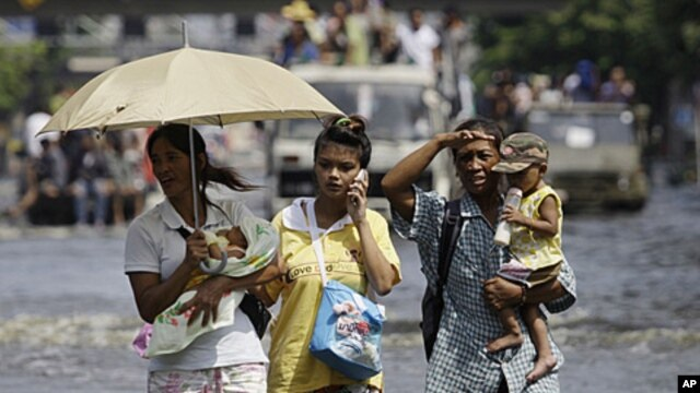 Thai residents carry children across flooded streets in Bangkok, Thailand,  November 6, 2011.