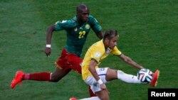 Pemain Kamerun Allan Nyom mengejar Neymar dari Brazil dalam pertandingan di stadion nasional Brasilia (23/6).